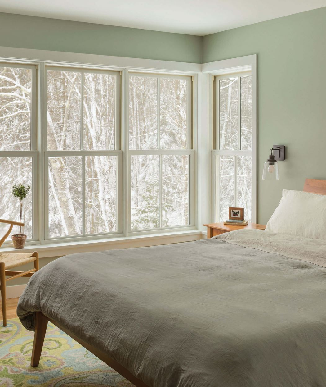 Bedroom in residential home with large white wood windows installed almost floor to ceiling